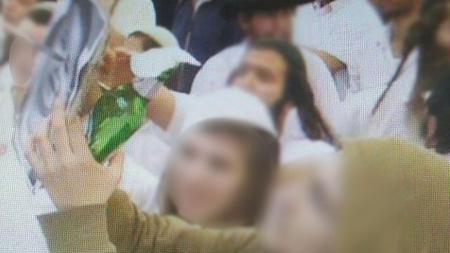 Right-wing activists stabbing murdererd Palestinian baby's picture during wedding. Rabbis are sending their frantic followers into the fire