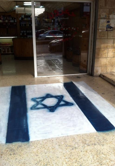 Israeli flag painted in front of a Jordanian shop so that clients can walk over it