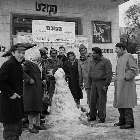 """Passersby pose with a snowman in front of the historic Mograbi Cinema, showing """"Hamlet"""" starring Laurence Olivier, on February 6, 1950 (Photo: David Eldan/GPO)"""