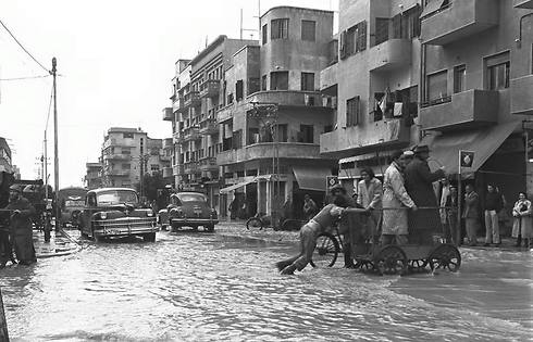 People cross the street on a cart on a flooded Shalma Street, 1949 (Photo: Fritz Cohen/GPO)