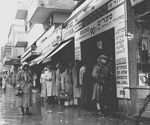 Crowd waits in the rain outside bookstore at 64 Allenby Street, offering books in Hebrew, English, Polish and French at a 90 percent discount, 1955 (Photo: Fritz Cohen/GPO)