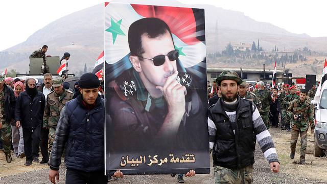 Syrians hold poster of Bashar Assad (Photo: AFP)