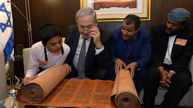 PM Netanyau with some of the group's members, and the antique torah scroll. (Photo: Haim Zach, GPO)