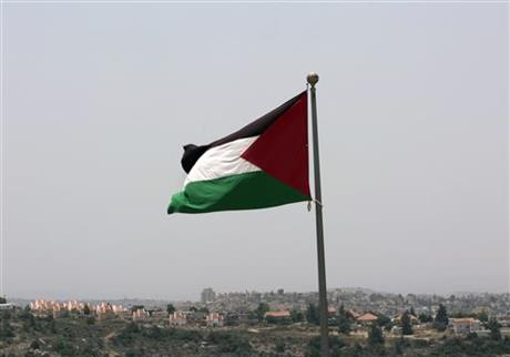 Israeli settlement Ateret in background as the Palestinian national flag flies from the highest point of Rawabi