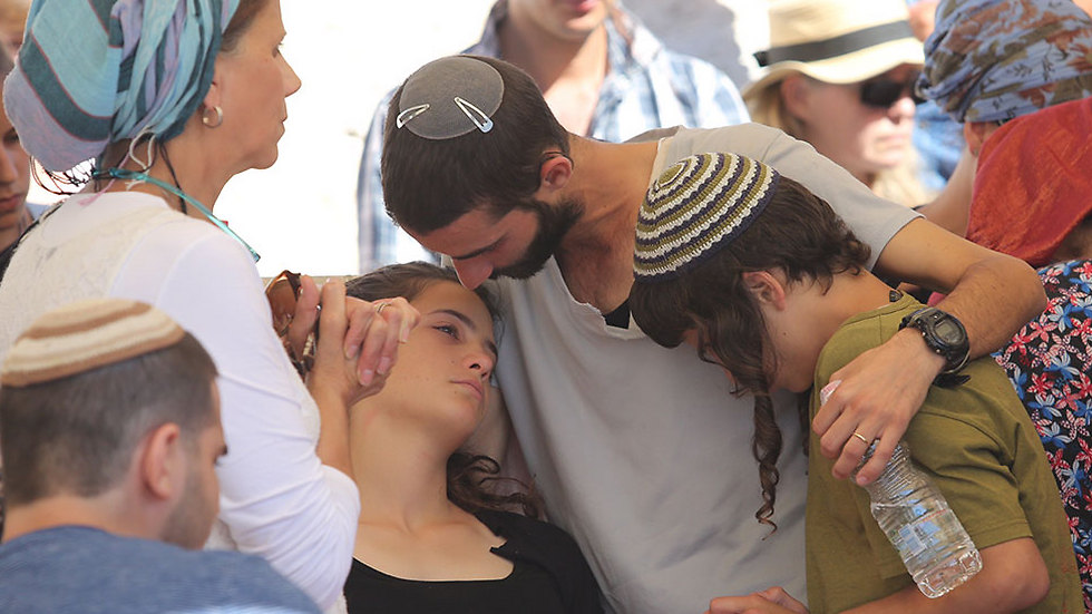 Tehila Mark embraced by her brothers Netanel (in white) and Pedayah (in green) during their father's funeral (Photo: Gil Yohanan)