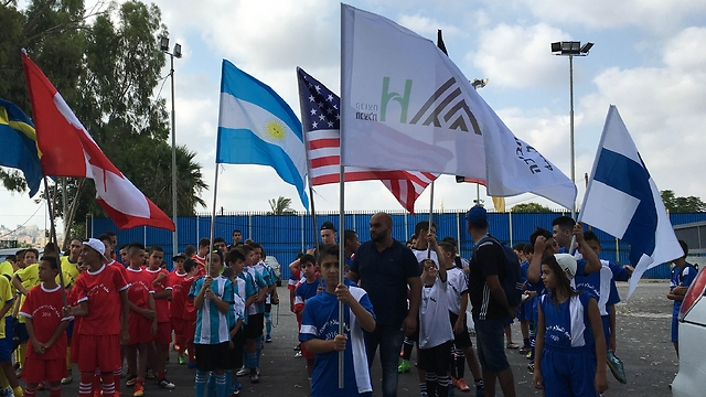"""Campers raising the flags of the countries """"competitng"""" in the tournament"""