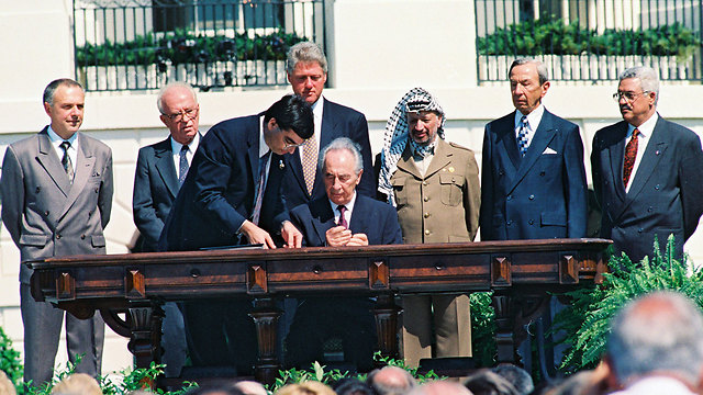 Peres, sitting, signing the Oslo Accords with Palestinian leader Yasser Arafat, US President Bill Clinton and Israeli Prime Minister Yitzhak Rabin looking on (Photo: Avi Ohayon, GPO) (Photo: Avi Ohayon, GPO)