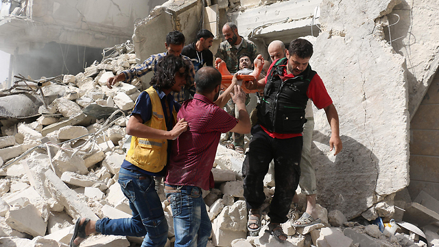 Evacuating the wounded from the wreckage in Aleppo following the recent onslaugh (Photo: AFP)