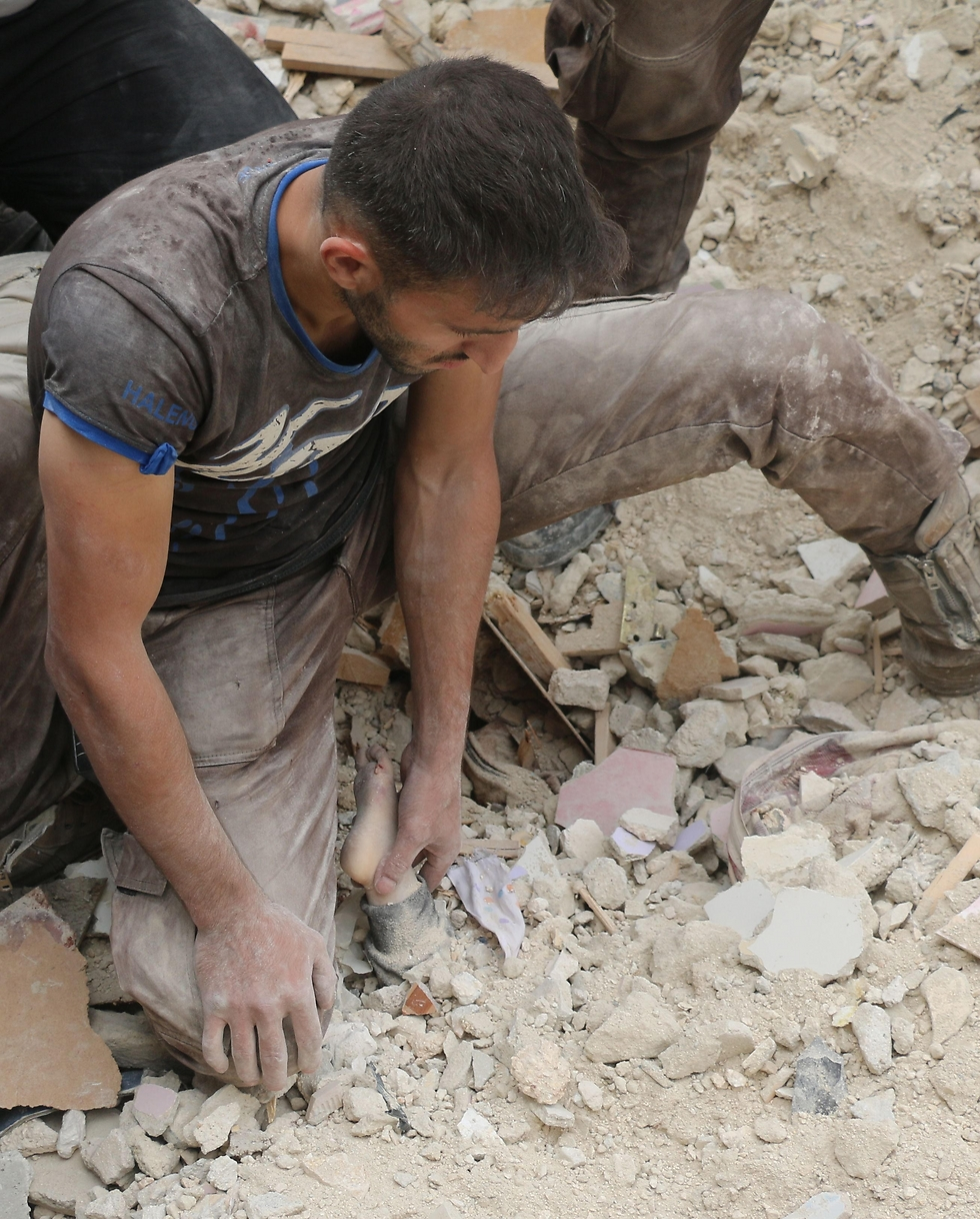 A man finds a child in rubble caused by a regime airstrike on Aleppo (Photo: AFP)