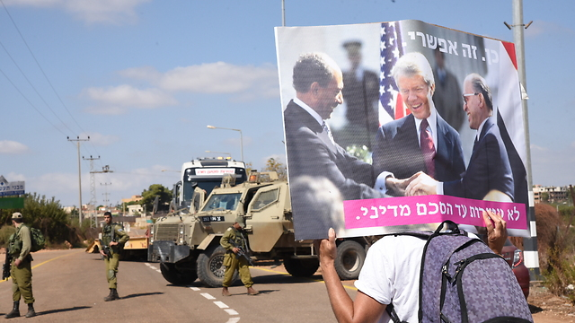 A protester carrying a sign with Mencahem Begin, Anwar Sadat and Jimmy Carter sign the Israel-Egypt Peace Treaty (Photo: Avihu Shapira)