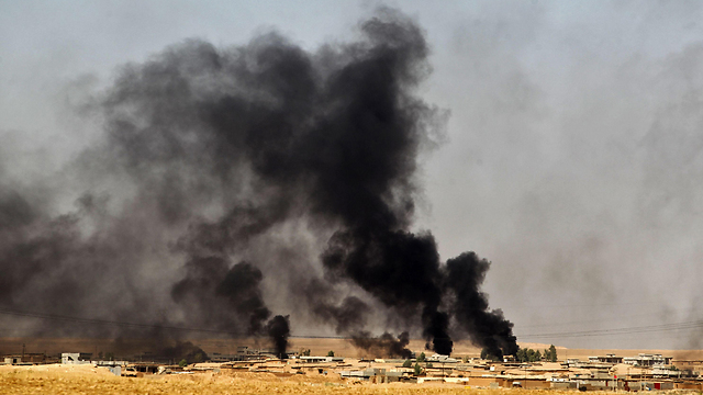 A village burns as Iraqi and Peshmerga forces approach Mosul (Photo: AFP)