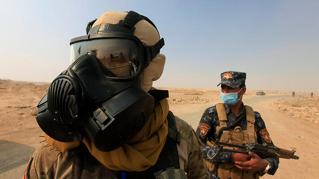 Soldiers don gas masks after ISIS lights sulpher plant on fire (Photo: Reuters)
