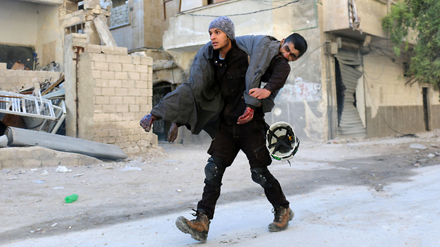 White Helmets activist rescuing a Syrian refugee in Aleppo  (Photo: AFP)