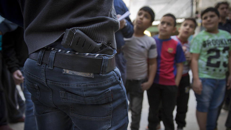 Palestinian refugee boys gather by armed men who are wanted by the Palestinian Authority security, one with a concealed weapon (Photo: AP)
