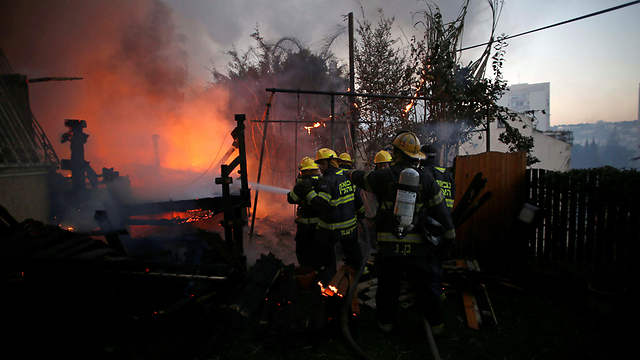 Firefighters battling the flames in Haifa on Thursday (Photo: Reuters)