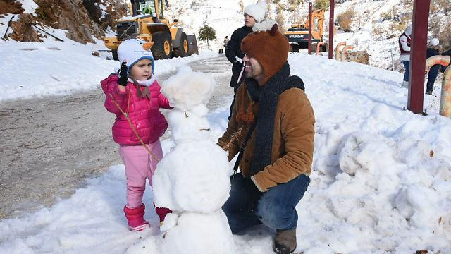 A man and his daughter build a snowman on Mt. Hermon (Photo: Aviyahu Shapira)
