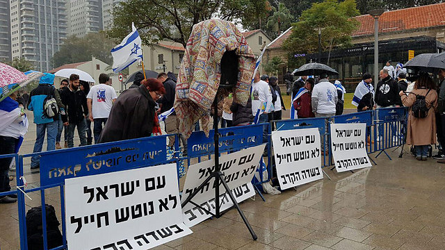 Protesters who arrived early waiting behind the barricades with signs that say 'The people of Israel don't abandon a soldier during battle'