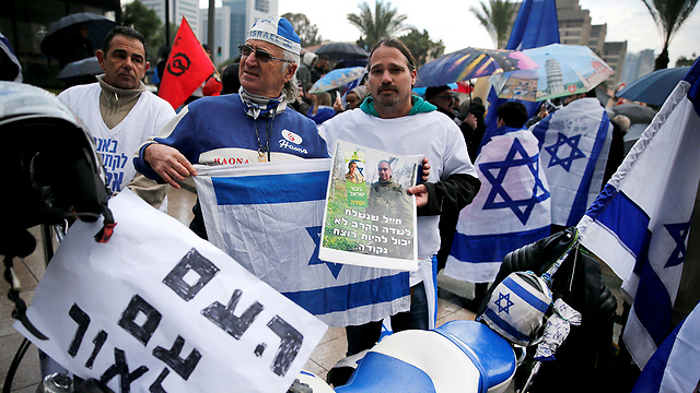 Protesters holding signs and Israeli flag, with one banner saying 'The people are with you Elor' (Photo: Reuters)