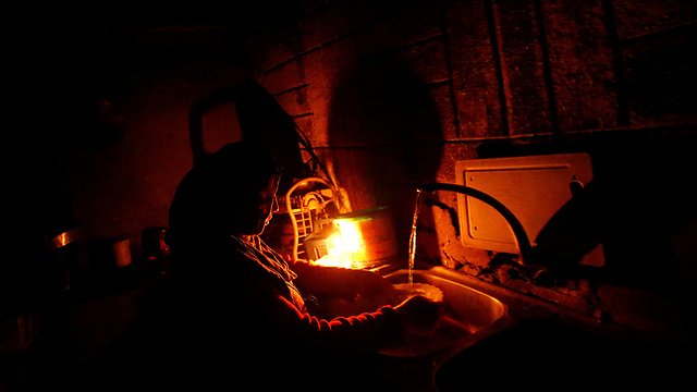 A Gazan woman washes dishes in the dark (Photo: Reuters)