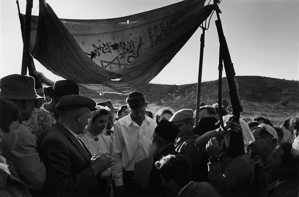 A makeshift Chuppah from 1952, held up by pitchforks and rifles (Photo: David Seymour)