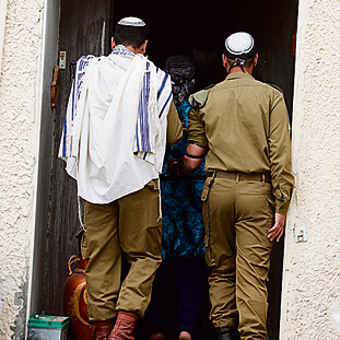 The two IDF soldiers at the entrance to their home. 'Tell us where peace is and we'll go get it' (Photo: Gadi Kabalo)