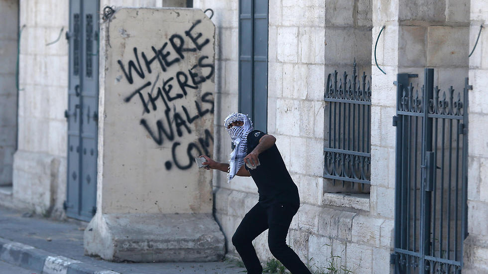 A Palestinian protester hurls stones towards Israeli security forces during clashes following a demonstration in the West Bank town of Bethlehem (Photo: AFP) (Photo: AFP)