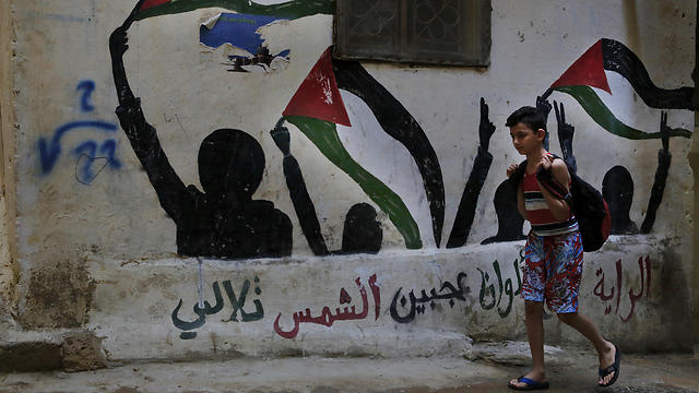 """In this Thursday, May 4, 2017 photo, a boy walks by graffiti of the Palestinian flags with Arabic reads: """"The flag is four colors that shine on the face of the sun"""" in the Bourj al-Barajneh Palestinian refugee camp in Beirut, Lebanon. (Photo: AP) (Photo: AP)"""
