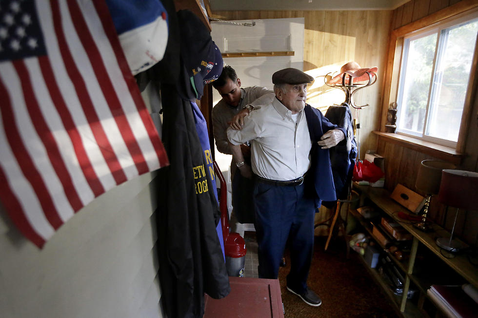 """Holocaust survivor Steve Ross, right, is helped with his jacket by his son Mike Ross, behind, as they prepare to depart Steven Ross' home in Newton, Mass., to attend the premier of the film """"Etched in Glass: The Legacy of Steve Ross."""" (Photo: AP) (Photo: AP)"""