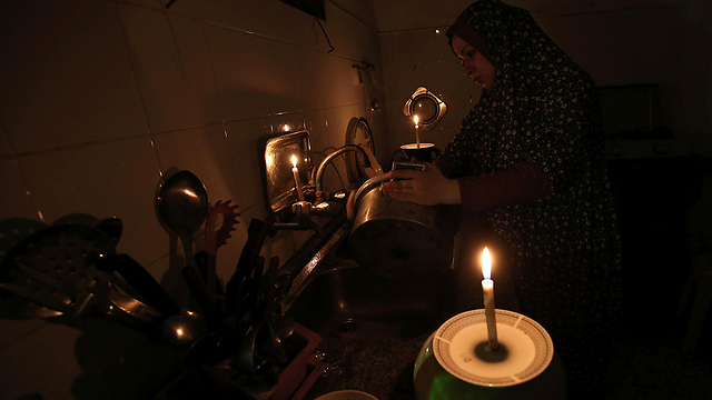 Woman washing dishes to candlelight during power outage (Photo: AFP)