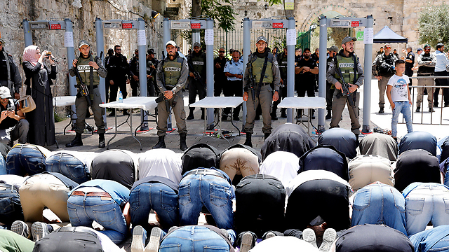 Palestinians praying outside Temple Mount in protest against new security measures (Photo: EPA)