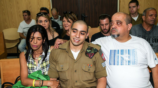 Azaria during his trial with his father Charlie and mother Oshra (Photo: Yariv Katz)