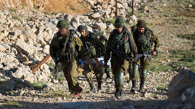 A wounded Syrian is carried by IDF troops to treatment (Photo: IDF Spokesperson's Unit)