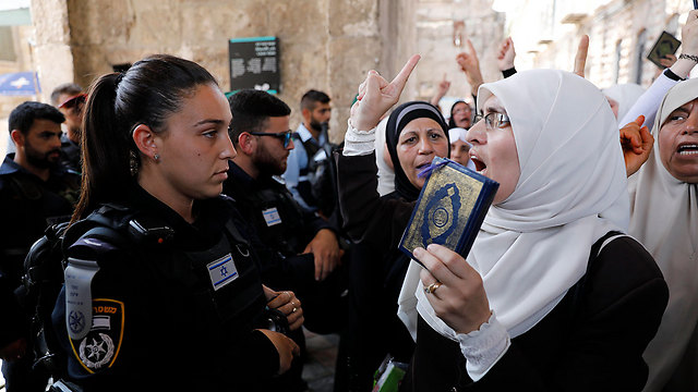 A Muslim protestor waves the Quran in front of an IDF police woman (Photo: EPA)