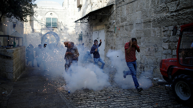 Worshippers fleeing clashes with police (Photo: Reuters)
