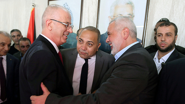 Palestinian PM Hamdallah (L) shakes hands with Hamas leader Haniyeh (Photo: Reuters) (Photo: Reuters)
