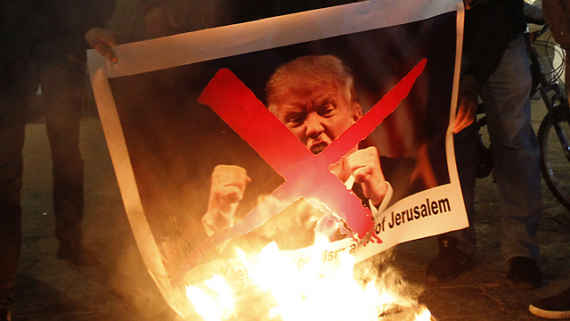 Protestors set fire to Trump's picture in Bethlehem following declaration  (Photo: AFP)
