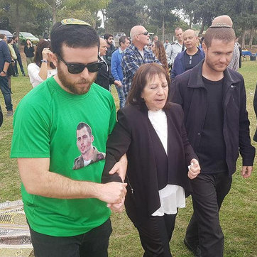 Zehava Shaul led away from the ceremony in honor of her son after rockets are fired from Gaza  (Photo: Moti Lavton)