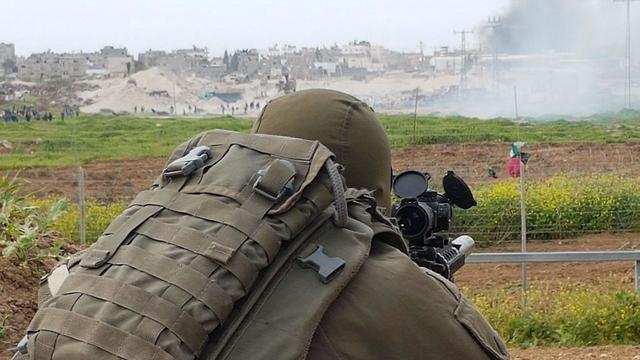 IDF sniper watches as Palestinian protestors riot on Gaza border (Photo: Yoav Zitun)