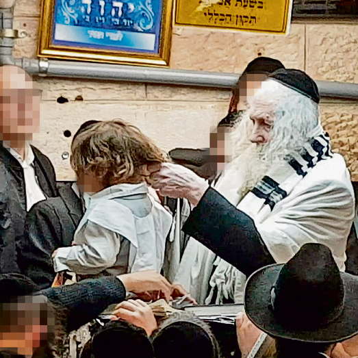 Berland performs the upsherin haircutting ceremony. 'We grew his hair long again, because when he was three years old the rabbi was absent'