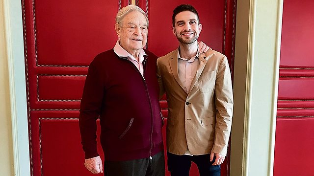 George and Alexander Soros in Berlin last week. 'My father is completely different from the image people have of him'  (Photo: Nahum Barnea)