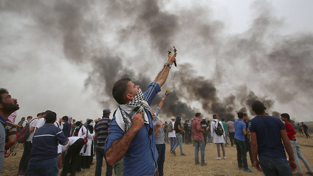 Palestinian rioter armed with slingshot aiming at a nearby hovering drone (Photo: AFP)