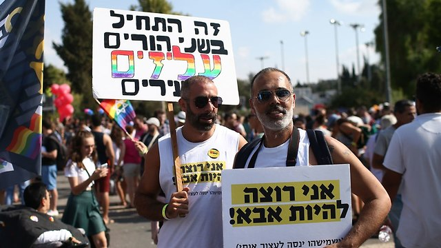 Two marchers, one with a sign saying 'It started with two parents, gay and young,' while the other's sign says: 'I want to be a father' (Photo: Ohad Zwigenberg)