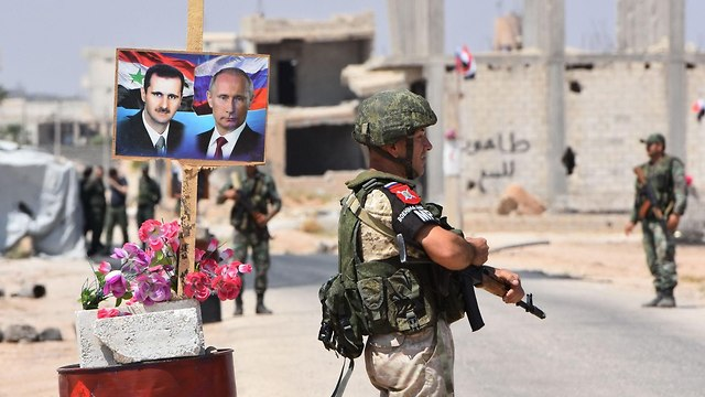 An image of Vladimir Putin appears alongside one of Bashar Assad at a Syrian military post. (Photo: AFP)