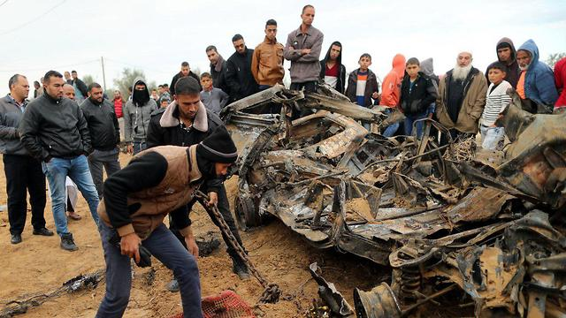 Gazans gather at the wreckage of vehicle used by IDF incursion forces in Gaza (Photo: Reuters)