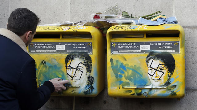 French street artist Christian Guemy cleans mailboxes vandalized with swastikas covering the face of the late Holocaust survivor and renowned French politician, Simone Veil, in Paris, Tuesday Feb. 12, 2019.