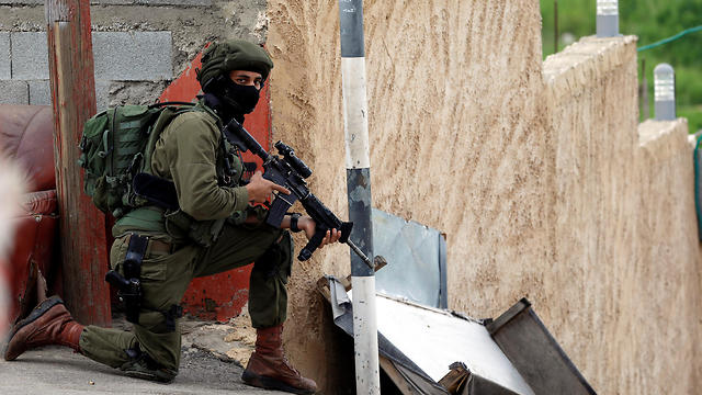 An IDF soldier searches for the Palestinian gunman near Nablus, March 17, 2019