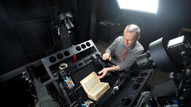 A man photographs ancient manuscript as part of a digitization process in St Catherine's Monastery