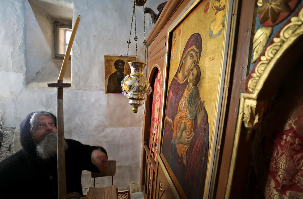 A monk adjusts a candle inside St Catherines Monastery
