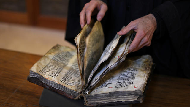Librarian Father Justin of Sinai turns pages of a manuscript in the library of St Catherine's Monastery