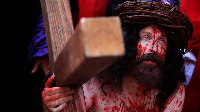 A Catholic pilgrim carries a cross along the Via Dolorosa as he re-enacts the passion of Jesus Christ on Good Friday (Photo: